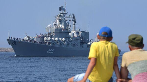 Мужчина с ребенком на набережной наблюдают за подготовкой кораблей ВМФ РФ к параду, посвященному Дню Военно-морского флота РФ, в Кронштадте