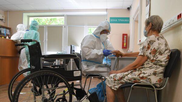 Медицинский работник с пациентом в госпитале COVID-19 в городской клинической больнице № 52 в Москве