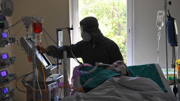 Медицинский работник у постели пациента в отделении реанимации и интенсивной терапии в госпитале COVID-19 в городской клинической больнице № 52 в Москве