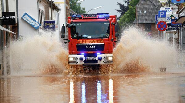 Пожарная машина проезжает по затопленной улице после проливных дождей в Эрфтштадте, Германия