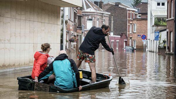 Люди плывут на лодке по жилой улице после наводнения в Англере, провинция Льеж, Бельгия