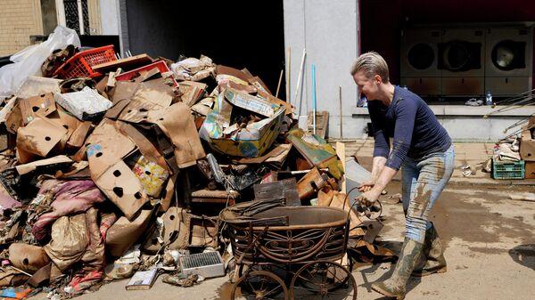 Женщина убирает повреждённые вещи после наводнения в Пепинстере, Бельгия