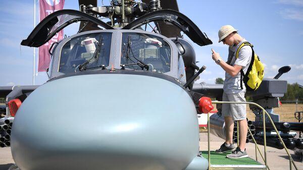 Посетитель фотографирует кабину российского разведывательно-ударного вертолета Ка-52 на Международном авиационно-космическом салоне МАКС-2021