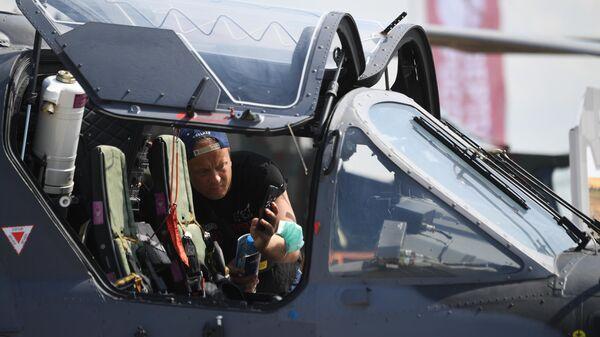 Посетитель фотографирует кабину российского разведывательно-ударного вертолёта Ка-52 на Международном авиационно-космическом салоне МАКС-2021