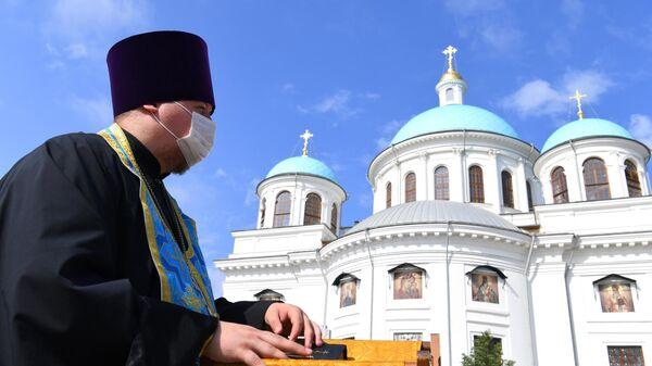 Священнослужитель на площади у воссозданного собора Казанской иконы Божией Матери в Казани