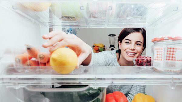Девушка достаёт лимон из холодильника