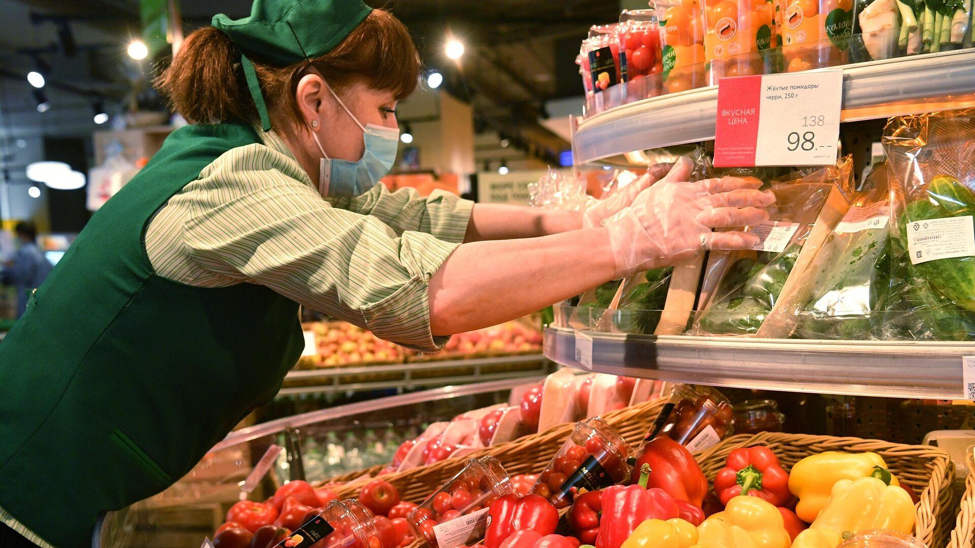Продавец выкладывает овощи на прилавок в магазине Азбука Вкуса в Москве - РИА Новости, 1920, 05.10.2021