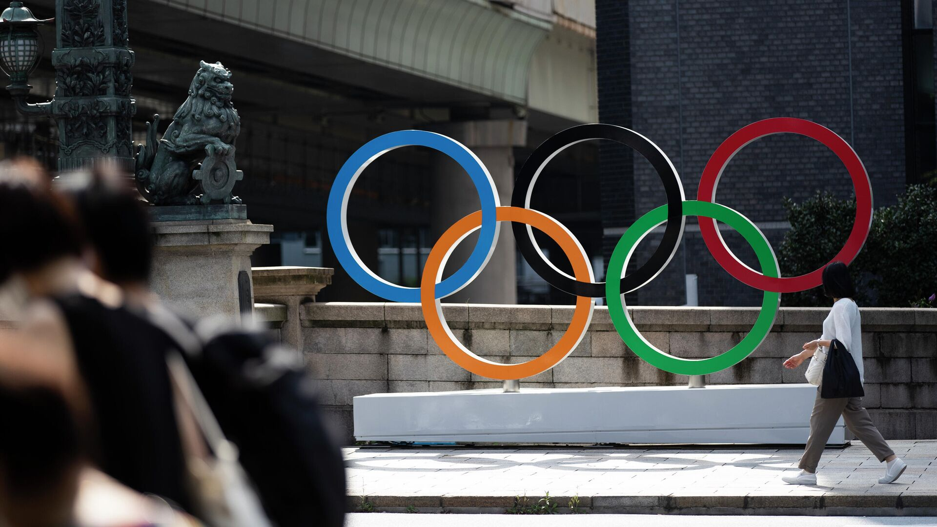 Женщина идет мимо олимпийских колец в Токио - РИА Новости, 1920, 22.07.2021
