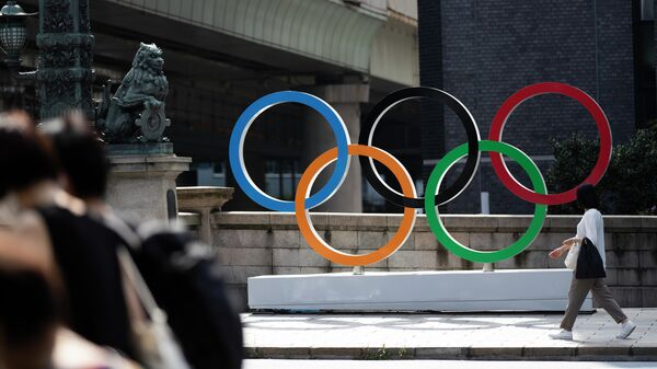 Женщина идет мимо олимпийских колец в Токио