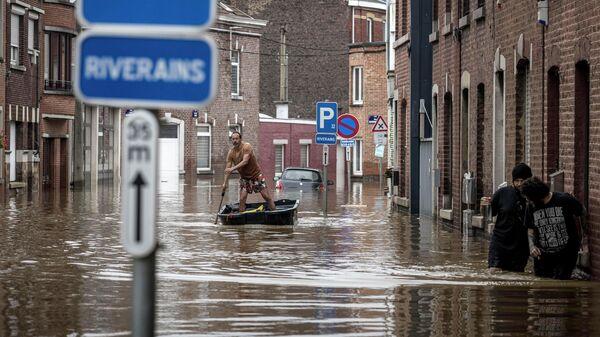 Мужчина плывет на лодке по жилой улице после наводнения в Англере, Бельгия