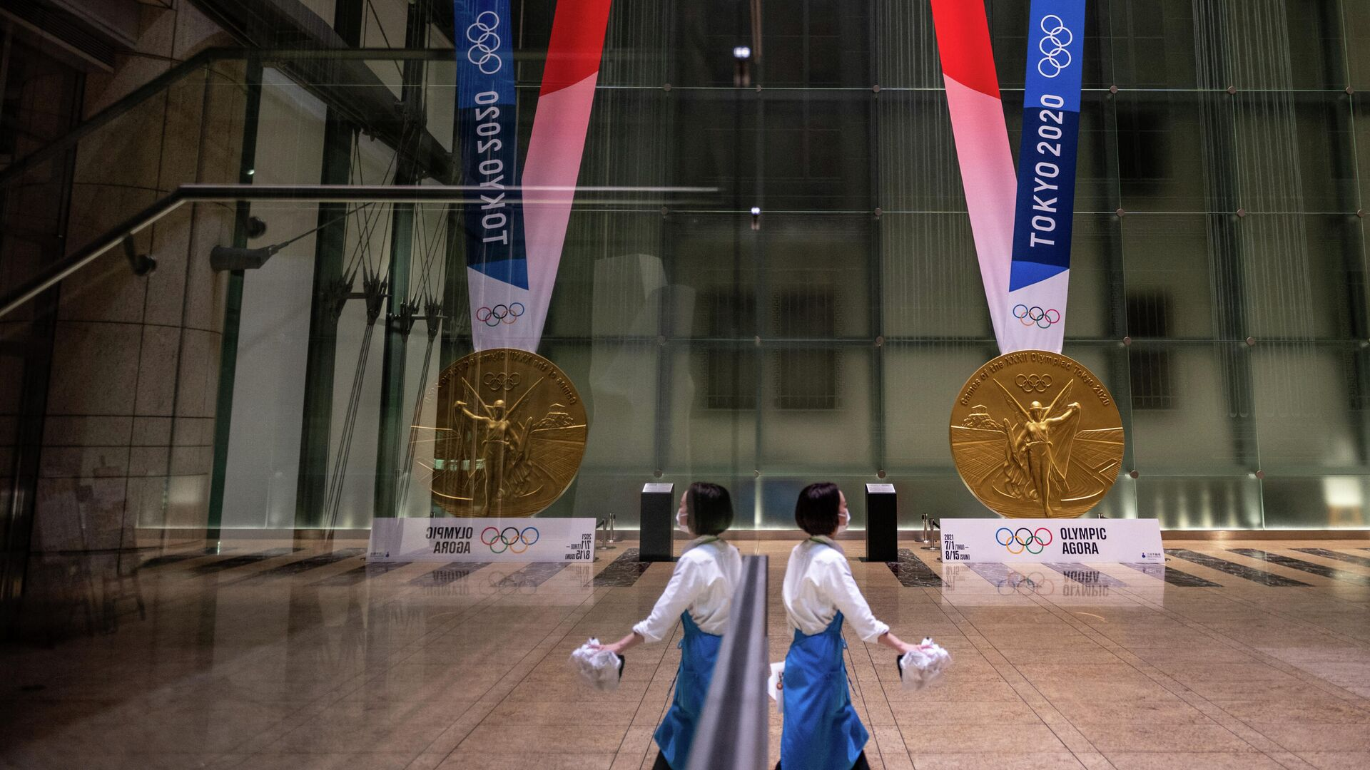 A woman walks near a large-scale reproduction of the Tokyo 2020 Olympic Games gold medal as part of the Olympic Agora event at Mitsui Tower in Tokyo on July 14, 2021. (Photo by Philip FONG / AFP) - РИА Новости, 1920, 23.07.2021