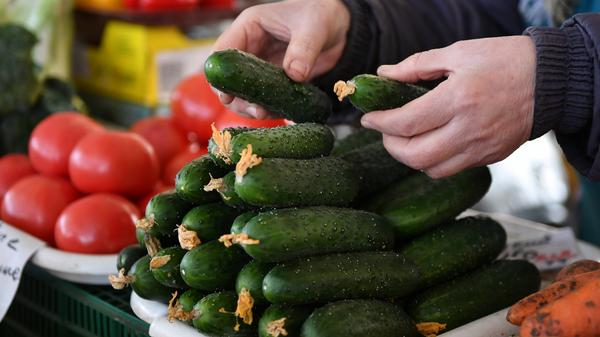 Продавец раскладывает овощи на прилавке