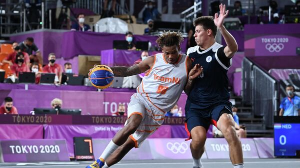 Netherlands' Jessey Voorn (L) fights for the ball with Russia's Kirill Pisklov during the men's first round 3x3 basketball match between Netherlands and Russia at the Aomi Urban Sports Park in Tokyo, on July 24, 2021 during the Tokyo 2020 Olympic Games. (Photo by Andrej ISAKOVIC / AFP)