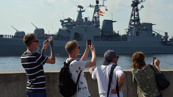 Люди на набережной наблюдают за подготовкой кораблей ВМФ РФ к параду в Кронштадте