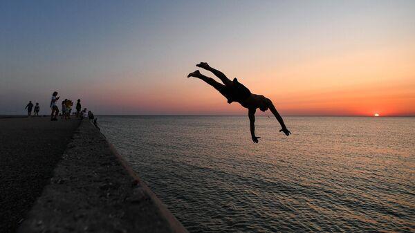 Мужчина прыгает с пирса в курортном поселке Новофедоровка Сакского района в Крыму