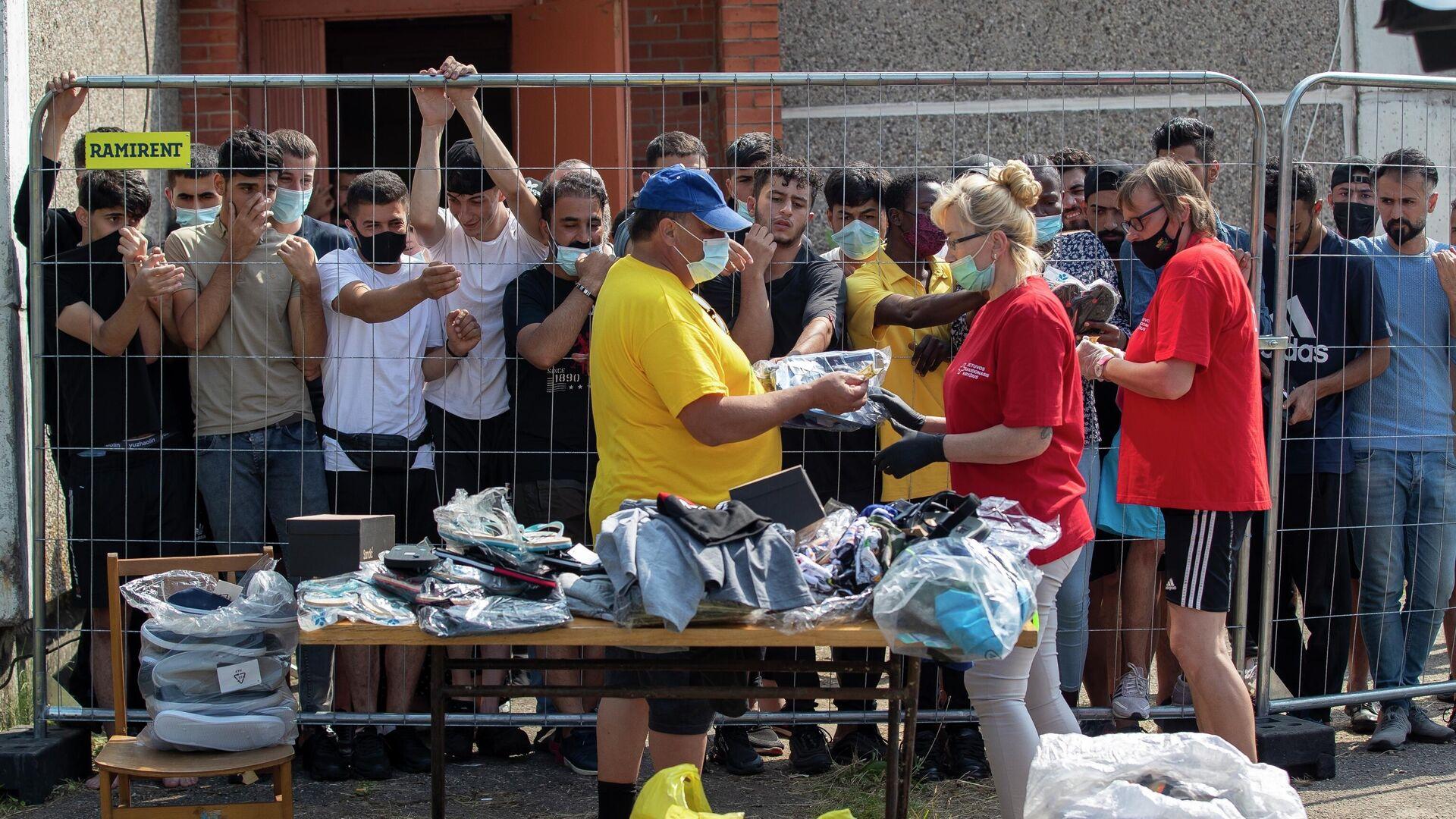 Литовцы продают вещи мигрантам в лагере беженцев в селе Веребежай в Литве - РИА Новости, 1920, 03.08.2021