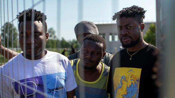 Мигранты из Камеруна стоят у забора в лагере беженцев в Литве