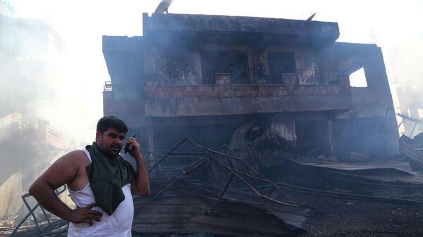 Мужчина возле сгоревшего дома в результате лесного пожара в Анталье, Турция