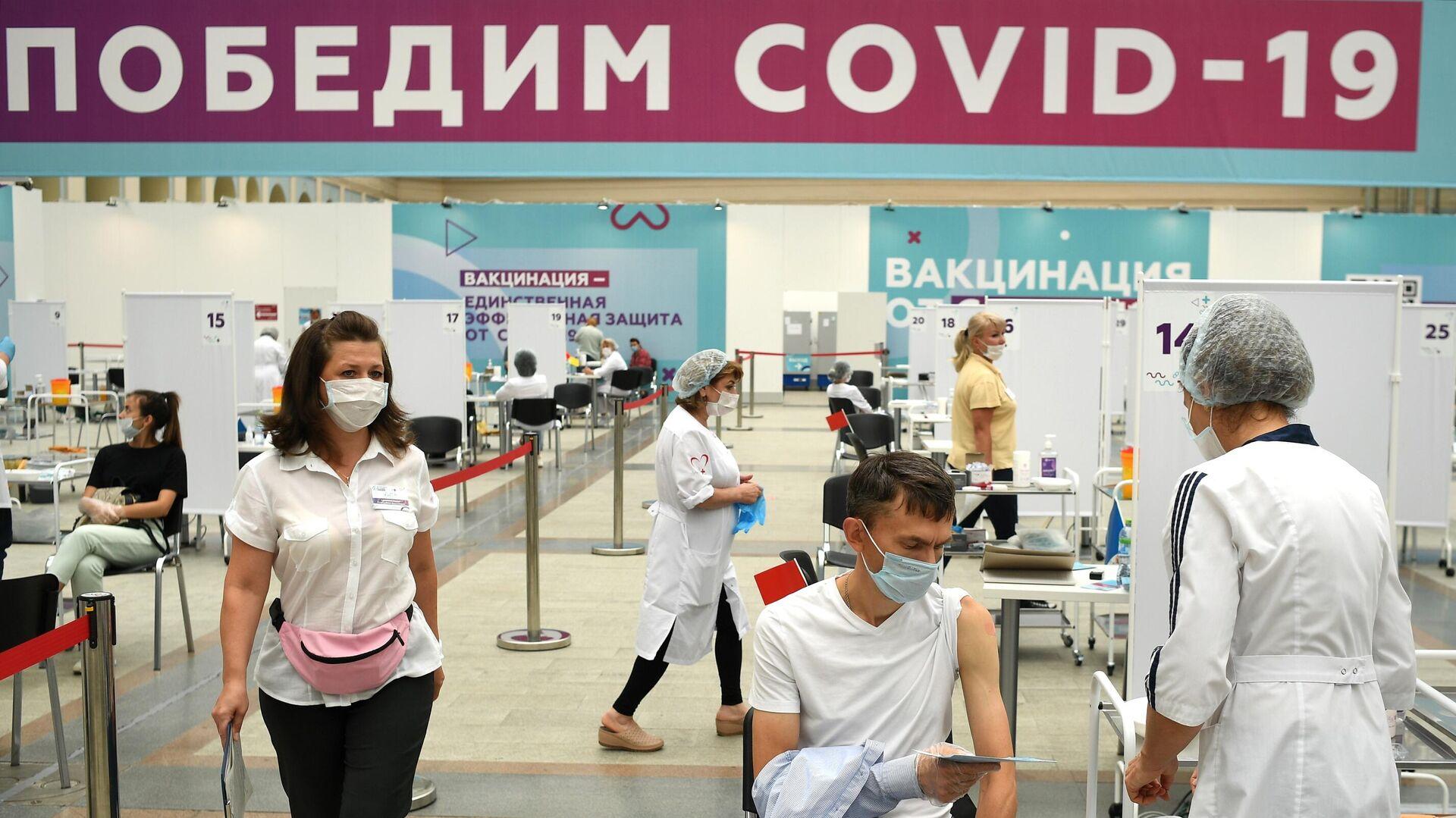 Посетитель делает прививку в центре вакцинации от COVID-19 в Гостином дворе в Москве - РИА Новости, 1920, 06.08.2021