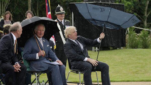 Британский принц Чарльз и премьер-министр Борис Джонсон укрываются от дождя во время открытия Мемориала полиции Великобритании в Национальном мемориальном дендрарии в Олревасе, Англия
