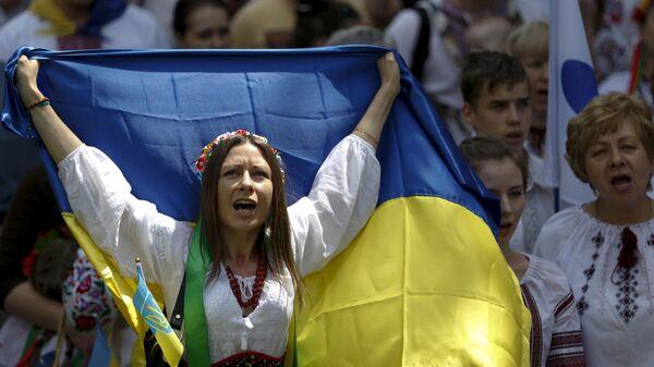 Женщина в вышиванке с украинским флагом на марше в Киеве, Украина