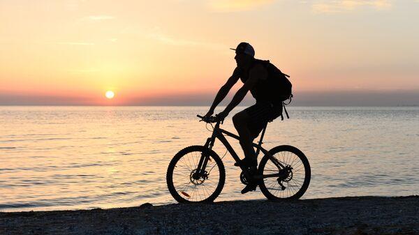 Велосипедист на берегу Азовского моря возле города Щелкино в Крыму
