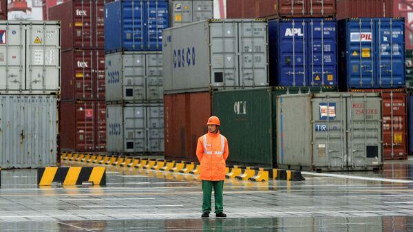 Рабочий стоит перед контейнерами в порту в Шанхае