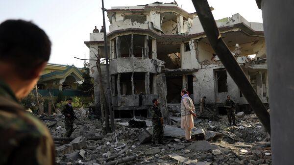 Сотрудники службы безопасности Афганистана осматривают здание, поврежденное после подрыва автомобиля в Кабуле