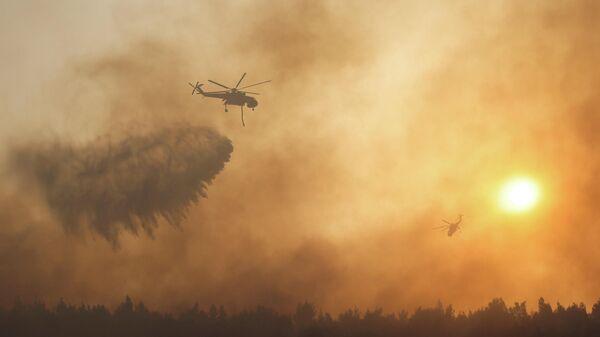 Пожарный вертолет во время тушения лесного пожара в пригороде Афин Варибоби