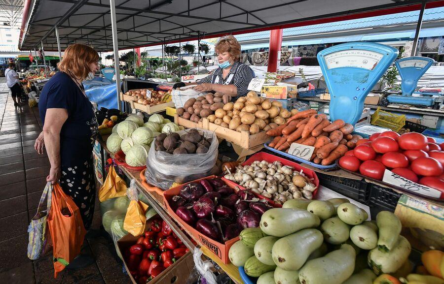Покупатель и продавец на овощном рынке