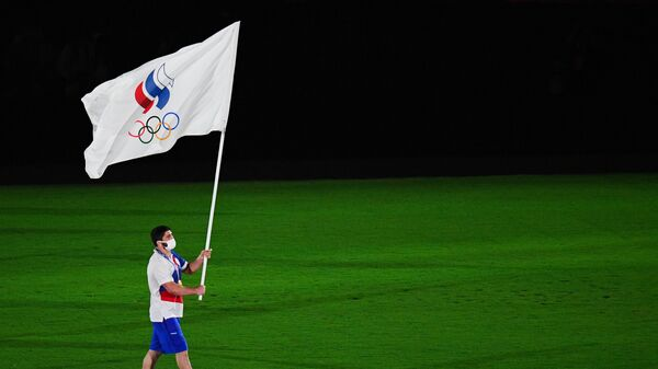 Знаменосец команды Олимпийского комитета России (ОКР), борец Абдулрашид Садулаев во время парада атлетов на торжественной церемонии закрытия XXXII летних Олимпийских игр в Токио на Национальном олимпийском стадионе