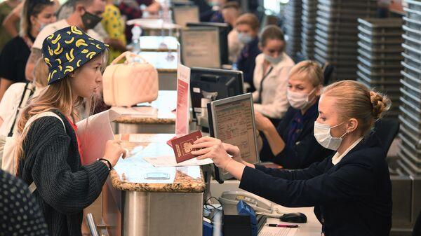 Сотрудница проверяет документы пассажира на стойке регистрации в аэропорту Шереметьево в Москве