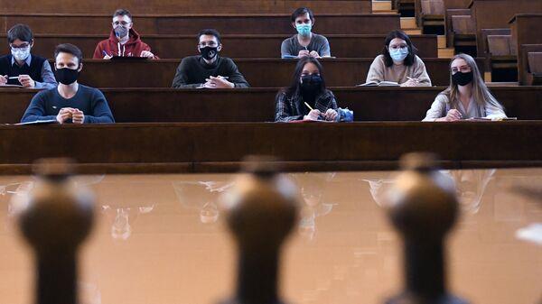 Студенты в защитных масках во время лекции в аудитории Московского государственного университета имени М. В. Ломоносова