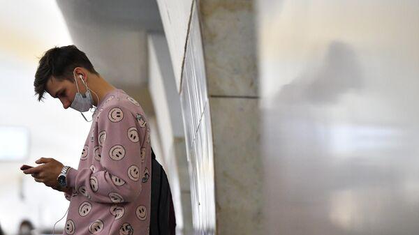 Юноша в маске на станции московского метрополитена