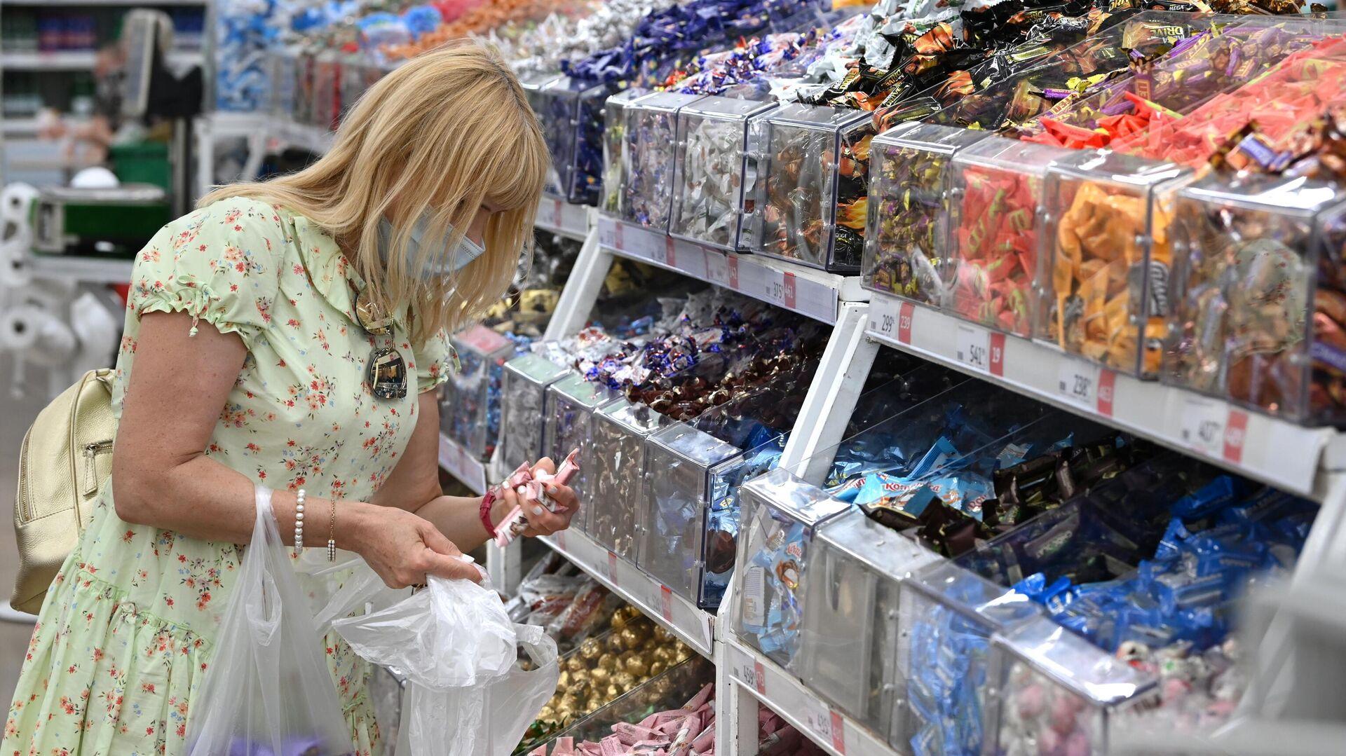 Девушка покупает конфеты в бакалейном отделе гипермаркета Ашан в Москве - РИА Новости, 1920, 07.09.2021