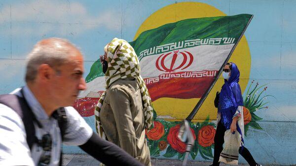 Иранцы в масках проходят мимо фрески с изображением национального флага Ирана в Тегеране