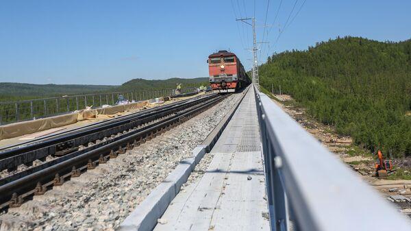 Поезд едет по реконструируемому в рамках строительства второй очереди Байкало-Амурской магистрали железнодорожному мосту через реку Кованта