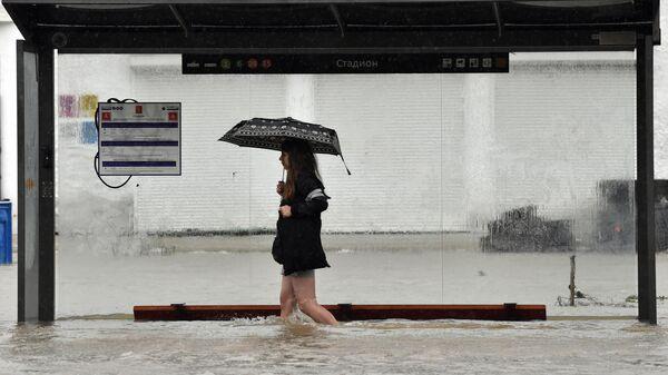 Девушка на подтопленной автобусной остановке в результате ливневых дождей улице в Керчи
