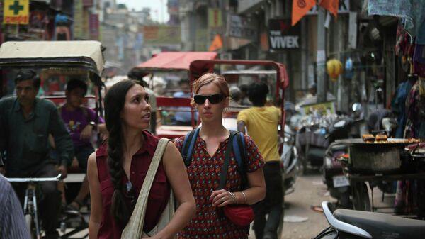 Туристы идут по улице возле железнодорожного вокзала в Нью-Дели, Индия