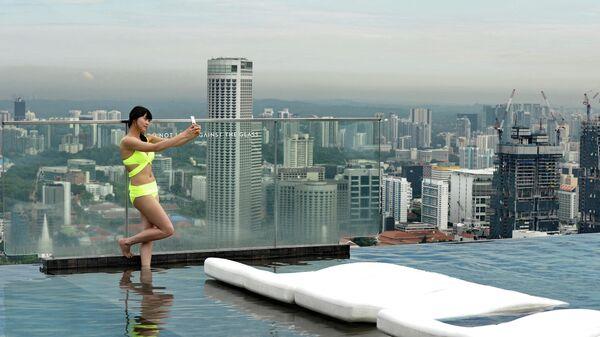 Посетительница бассейна на крыше небоскреба в Сингапуре