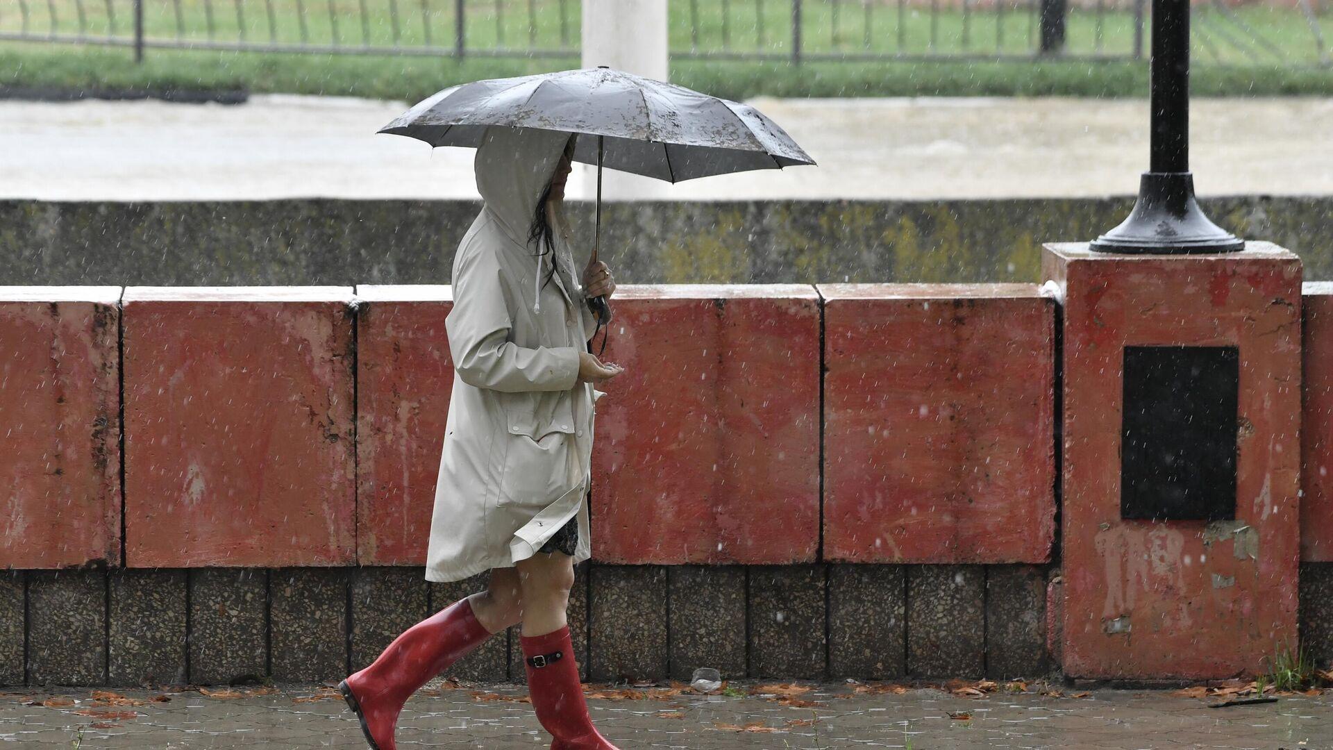 Женщина под зонтом на улице в Керчи - РИА Новости, 1920, 15.09.2021