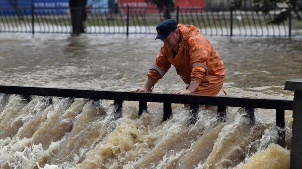 Сотрудник коммунальной службы на подтопленной в результате ливневых дождей улице в Керчи