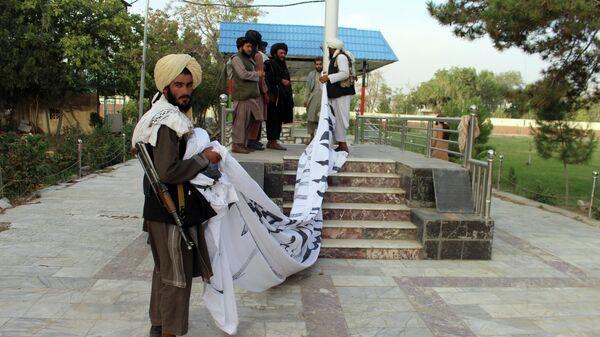 Боевики Талибана* поднимают свой флаг у резиденции губернатора провинции Газни, юго-восток Афганистана