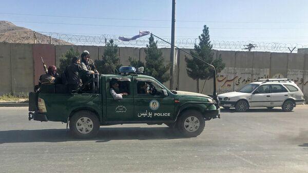 Боевики Талибана* едут на полицейской машине в Кабуле, Афганистан