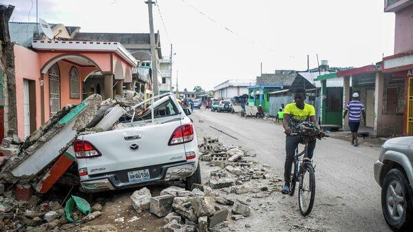 Поврежденный автомобиль под обломками после землетрясения в Гаити