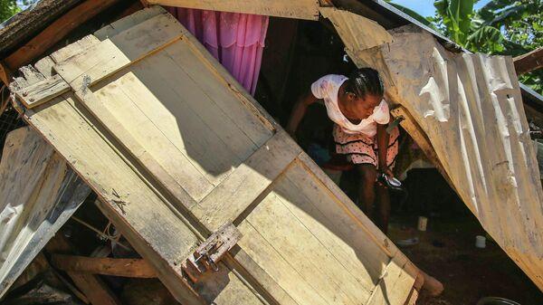 Женщина среди обломков своего разрушенного землетрясением дома, Гаити