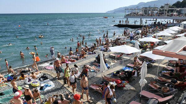 Отдыхающие на берегу Черного моря в Ялте