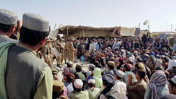 Солдаты пакистанской армии разговаривают с людьми, которые собираются пересечь пункт пропуска в пакистано-афганском пограничном городе Чаман
