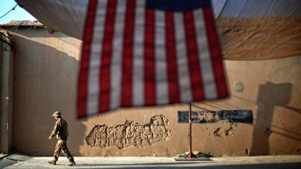 Солдат армии США проходит мимо американского флага на передовой оперативной базе Бостик в афганской провинции Кунар
