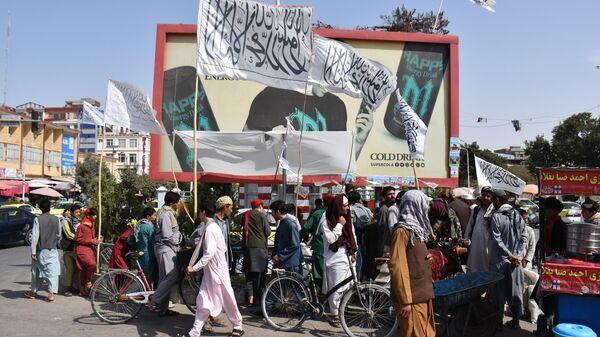 Люди с флагами движения Талибан* в городе Мазари-Шариф